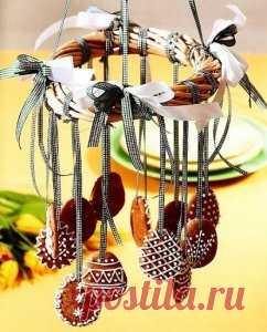 Идея вкусного праздничного декора для Пасхального стола.  Для этого надо из веток или лозы сплести небольшой венок, скрепить его в нескольких местах проволокой, украсить лентами пасхальным печеньем и подвесить над праздничным столом (например, на люстру).