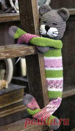 Вязаный кот, который очень любит обнимашки! Вам потребуется: остатки пряжи серого, зеленого, белого и черного цветов, немного меланжевой пряжи, синтепон, крючок № 2. Длина игрушки: 30 см Плотность вязания: 24 п. х 28 рядов – 10 х 10 см. Голова: серой нитью свяжите цепочку из 4 возд. п.