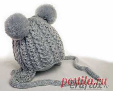 Tejido por los rayos el gorro infantil invernal con las orejitas y los pompones para la muchacha. El modelo, el esquema y la descripción.