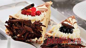 Чизкейк с белым шоколадом   Шоколадное печенье — 200 г  Масло сливочное — 2 ст. л.  Белый шоколад — 150 г  Мягкий сливочный сыр — 600 г  Сметана — 300 г  Сахар — 1 стак. Яйца (крупные) — 3 шт. Сливочный ликер — 60 мл   Для украшения:  Шоколадная стружка — по вкусу Взбитые сливки — по вкусу Свежие ягоды — по вкусу  Приготовление:  1. На дно разъемной формы для выпечки диаметром 24 см положите пергаментный круг, стенки выстлите пергаментной лентой, ширина которо...