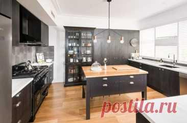 Мебель из окрашенного в черный цвет дерева в сочетании с акцентами из натурального дерева придает этой современной кухне, созданной дизайнерами интерьеров, атмосферу современного фермерского дома.