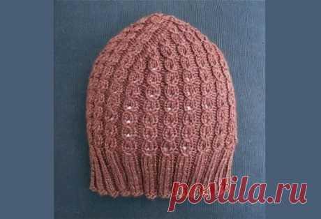 Розовая женская шапка Трюфель спицами с описанием вязания Схема и описание вязаной на спицах шапочки Трюфель с имитацией косичек. Очень простая и красивая модель по кругу ажурной резинкой.
