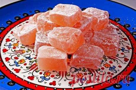 Рахат Лукум  Ингредиенты: -3 стакана сахара, -6 стаканов воды, -3 стакана крахмала, -1/2 стакана очищенных орехов (миндаля, фундука или любых других, на ваше усмотрение), -1/2 стакана сахарной пудры.  Приготовление: Очищенные орехи разделяем на половинки. Крахмал разводим холодной водой (3 стакана), размешиваем, чтобы не было комочков, и оставляем на некоторое время. В кастрюлю засыпаем сахар, заливаем его оставшейся водой и, время от времени помешивая, доводим до кипения,...
