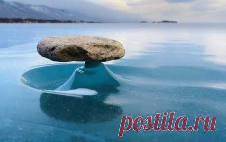 А это интересное явление происходит на озере Байкал. Дело в том, что днем камни нагреваются от солнечного света и лед под ними тает, как только солнце уходит, лед снова становится твердым и получается своеобразная подставка под камень. Называется Байкал-дзен