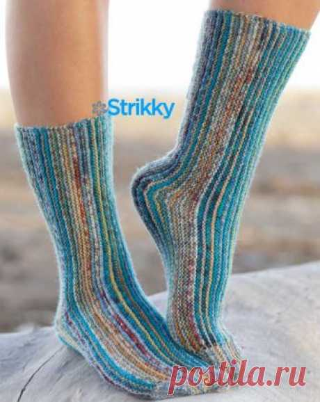 Женские носки от Drops Design вязаные спицами Носки вяжутся спицами поперёк, и этим данная модель от Drops Design отличается ото всех других моделей носков, выполненных традиционным способом. Основной узор – платочная вязка (пл/в). Цветовая гамма изделия переменная, создаётся чередованием двух меланжевых нитей, среди которых непременно присутствуют сине-бирюзовые оттенки.