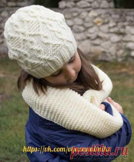 Комплект шапка и шарф спицами  Практичный и красивый комплект, молочного цвета. В комплект входит шарф, вязаный простым узором из лицевых петель, и шапочка с рельефным узором из жгутов и ромбов. Комплект выполнен из акриловой пряжи с добавлением шерсти, поэтому получился выразительным и фактурным. Кроме того, комплект достаточно теплый. Шапочка глубоко садится на голову, а мягкий шарф согреет шею и плечи.  Информация о шаблоне  Вес пряжи  3 - Light  Плотность вязания  17 п...
