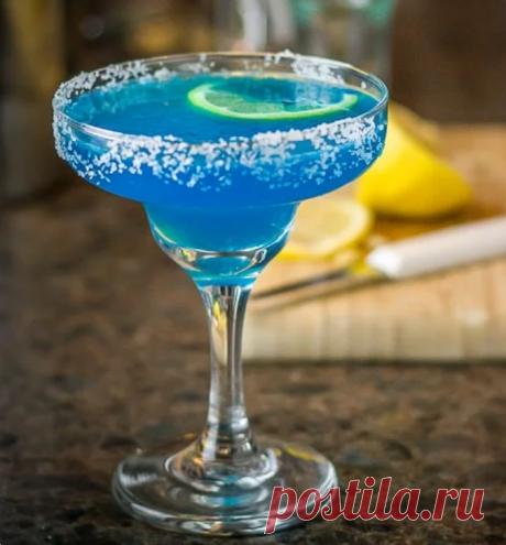 Коктейль Голубая Маргарита (Blue Margarita) Ингредиенты: 1. Лед 2. Cеребряная текила - 40 мл 3. Ликер «Blue Curacao» - 20 мл 4. Лимонный сок - 40 мл 5. Долька лайма (для украшения)