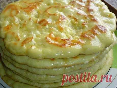 Хачапури по-тбилисски Ингредиенты: -Мука пшеничная 3 стакана -Кефир 1 стакан -Яйцо куриное 2 шт. -Соль 1 ч.л. -Сахар 1 ч.л. -Сода пищевая 0,5 ч.л. -Масло растительное 1 ст.л. -Сыр твердых сортов 400 г -Масло сливочное 50 г В кефир добавляем одно яйцо, сахар, соль и растительное масло, хорошенько перемешиваем. стакана муки просеиваем (один стакан муки оставляем для подсыпки), добавляем соду, перемешиваем и соединяем с кефирной массой. Замешиваем мягкое тесто, подсыпая понем...