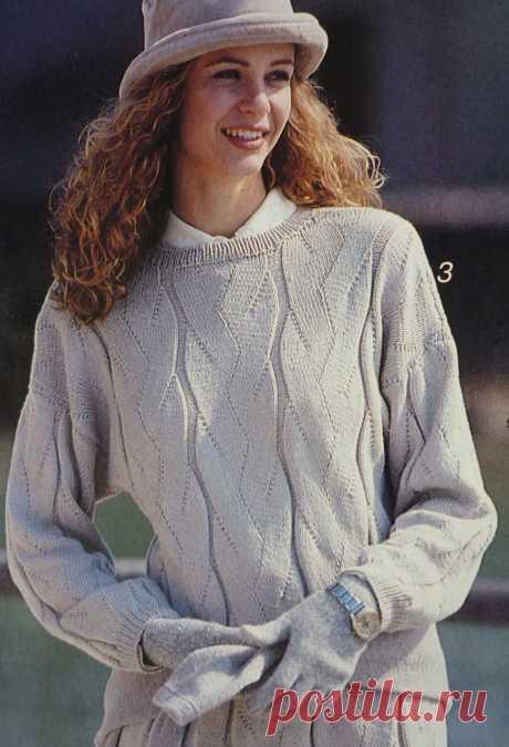 Светло-серый пуловер связан оригинальными рельефными дорожками с ажуром.Спицы