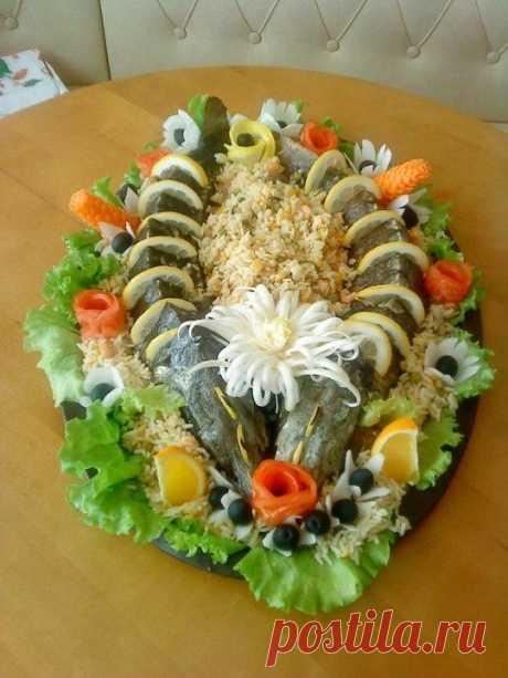Запеченная рыба с овощами в духовке. Запеченная с овощами в духовке праздничная рыба, очень вкусна и ароматна, ее можно подавать как горячей так и в холодном виде. При подаче обязательно украсить свежей зеленью, каперсами, оливками, лимоном и различными солениями.Запеченная рыба наверняка станет центральным блюдом на праздничном столе потому нужно старательно подойти к процессу приготовления и выбору самой рыбы.  Для праздничного блюда из рыбы как нельзя лучше подходят те сорта,