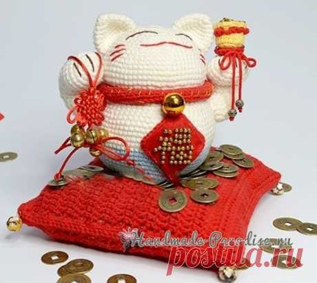 Maneki-neko el gato monetario por el gancho. La descripción de la labor de punto