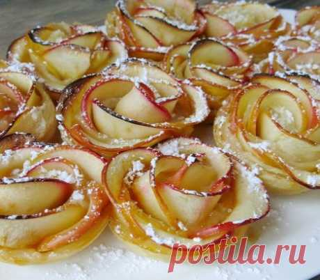 Прелестнейший десерт «Английская роза»  Бездрожжевое слоеное тесто — 250 г Яблоки красные крупные — 2 шт. Сахарная пудра — 1 ст. л. Сахар — 100 г Приготовление: 1. Яблоки разделить на 4 части, удалить сердцевину, нарезать очень тонкими дольками по 2 мм. 2. Запарить дольки в горячем сахарном сиропе до мягкости (3-5 минут). Достать и остудить. 3. Тесто тонко раскатать, нарезать полоски 2 см на 30 см. 4. На полоску положить дольки яблок, завернуть рулетиком, конец теста подогнуть по