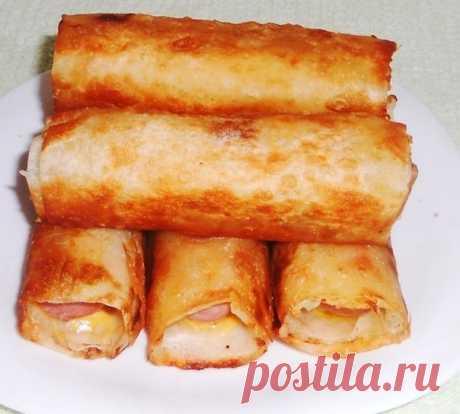 """Сосиски в картофельно-сырной """"шубке"""" и хрустящей корочке.  Нам понадобится (на 6 сосисок) 1 лаваш 4 средних картофелины 6 сосисок небольшой кусочек сыра 50 гр сливочного масла  Картофель почистить, отварить.  Лаваш нарезать прямоугольничками в ширину сосиски и длинной 15-20 см. сыр натереть на терке. Картофель потолочь, добавить соль, перец, сливочное масло. На лаваш намазать картофельное пюре тонким слоем, присыпать сыром, на край положить сосиску и свернуть рулетом. Таки..."""