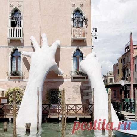 """""""Поддержка"""", скульптура Венецианской биеннале Лоренцо Куинна в 2017 году, изображающая пару колоссальных рук, поднимающихся из Гранд-Канала, кажется, поддерживает отель Ca' Sagredo."""