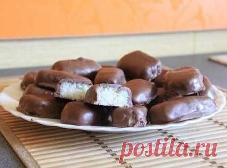 """Как быстро приготовить десерт. Конфеты """"Баунти"""".  Ингредиенты:  - Кокосовая стружка – 3 стакана - Сгущенное молоко – 200 г - Сахарная пудра – ½ - ¾ стакана - Ванилин – 1 чайная ложка - Горький шоколад – 350 г (растопленный на водяной бане)  Приготовление:  Кокосовую стружку смешайте со сгущенным молоком. Добавьте сахарной пудры столько, чтобы смесь была достаточно густой. Добавьте ванилин, перемешайте до однородной массы. Слепите небольшие шарики и поставьте в холодильник ..."""
