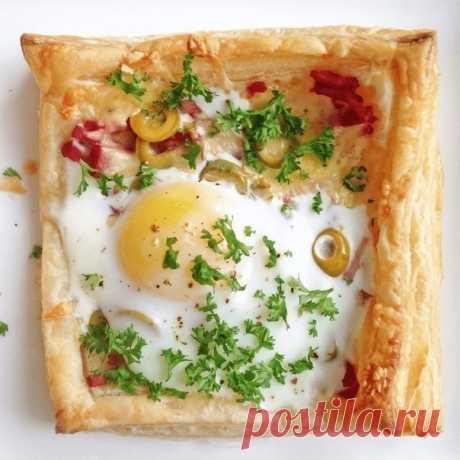 Слойки с яйцом, ветчиной и сыром  Ингредиенты (для 2 шт.):  Слоеное тесто — 1 лист Твердый сыр — 50 г  Ветчина — 50 г  Несколько оливок Яйца — 2 шт. Пара веточек петрушки Соль, перец  Приготовление:  1. Тесто раскатываем в одном направлении. Вырезаем 2 квадрата со стороной около 15 см и выкладываем на коврик для выпечки или застеленный пергаментом противень. Слегка надавливая ножом, обводим бортик, отступая от края около 1 см ( не прорезая тесто до конца). Внутри накалывае...