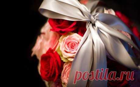 Букет из розовых и красных роз, перевязанный серебряной лентой.