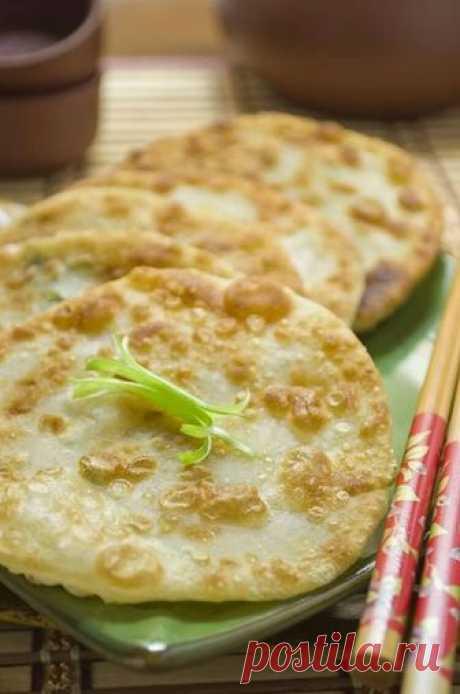 Китайские лепешки с зеленым луком: Хрустящая корочка и мягкая текстура внутри, слегка солоноватый аромат хлеба в сочетании с запахом зеленого лука       Ингредиенты:   225 г. муки 150 мл. кипятка 1 ч.л. кунжутного масла 4 перышка зеленого лука   Приготовление:  1.Просеиваем муку в миску. Добавляем соль, кунжутное масло и кипяток и очень быстро з…