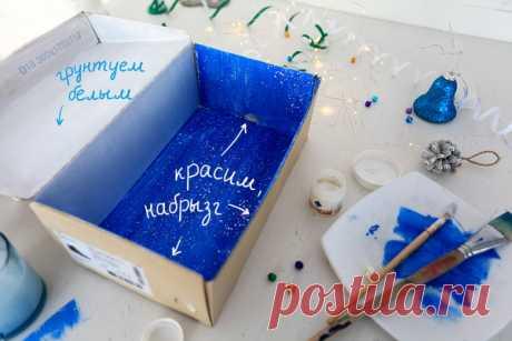 Приступим! Коробку и откидывающуюся крышку грунтуем внутри белым акрилом. Когда первый слой подсохнет, красим дно коробки и три стенки синим цветом — как показано на фото. С помощью белой краски и кисточки (или зубной щетки) «разбрызгиванием» снег.