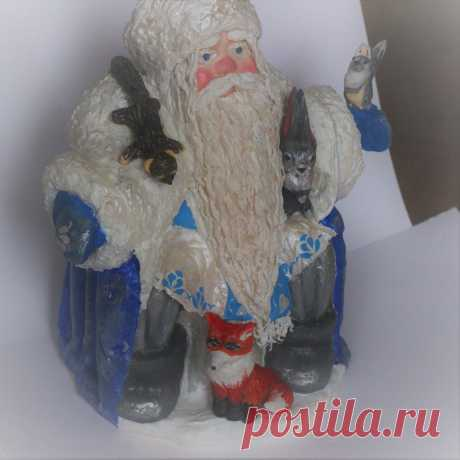 Дед Мороз который  сидит на пенёчке в окружении лесных зверей. Он в синей шубе, с длинной белой бородой и в валенках. Сделан из ваты.