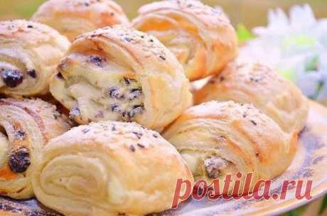 Топ-9 рецептов вкуснейшей выпечки Слоёнки с творожной начинкой и изюмом Ингредиенты: - Тесто слоеное бездрожжевое 400 гр - творог 400 гр - сахар 3-4 ст л - ванилин 1/3 ч л - яйцо сырое 1 шт -сметана 1-2 ст л - изюм б/косточек по вкусу - яйцо для смазки - сахарная пудра и кунжут для посыпки Приготовление: Смешать творог, 1 яйцо, сметану, ванилин и распаренный обсушенный изюм. Тесто разморозить, разрезать на 2 части. Раскатать в прямоугольник 15 на 35 см. Смазать половиной нормы начинки, не
