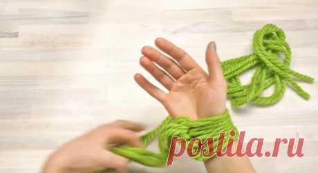 Женщина обмотала пряжу вокруг руки. Когда она закончила работу, у нее получился роскошный зимний аксессуар (видео)