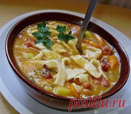 Фасолевый суп с домашней лапшой- вкусный обед.  Ингредиенты: - 400 гр фасоли - 150 гр колбасы - 150 гр бекона, ветчины или копченой свинины - 200 гр картофеля - 150 гр моркови - 50 гр лука-порей - зелень (петрушка, сельдерей, сухой красный перец) - чеснок, соль - по вкусу  Для приготовления домашней лапши: - 500 гр муки грубого помола - 2 яйца - 200 мл воды - соль   ...