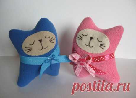 Las almohadas de la gata por las manos con los patrones y los esquemas