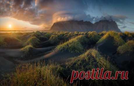 «Вечер на чёрных дюнах» Лентикулярное облако облюбовало одну из вершин горного хребта Вестрахорн, мыс Стокснес (Исландия). Автор фото – Михаил Щеглов: nat-geo.ru/community/user/120111