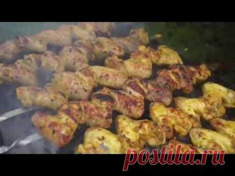 Las alitas jugosas de gallina sobre el brasero