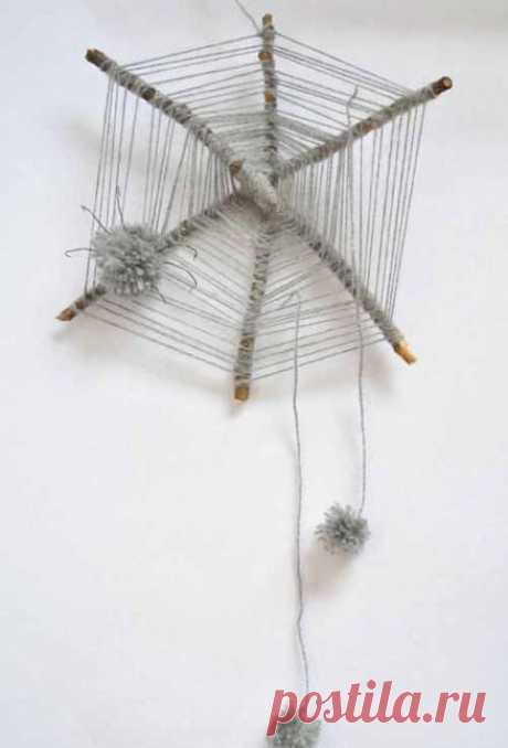 Decorative web from branches with spiders from pompons.