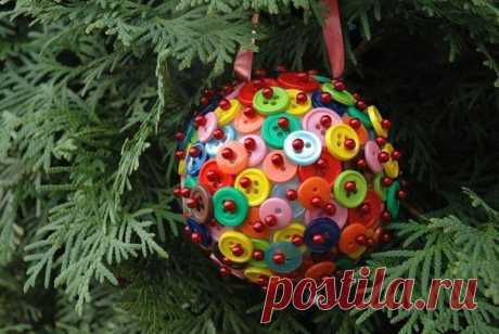 Необходимые материалы: многоцветные кнопки; пенопластовый шарик; палочки для еды с красивой головой; декоративная лента. производство: Сделать такое елочное украшение довольно просто. Для этого мы прикрепляем петлю красивой декоративной ленты к пенопласту, за которую ее можно повесить. Затем мы натягиваем одну или две кнопки на палочке и просто вставляем ее в шарик. Мы продолжаем покрывать шар кнопками, пока они полностью не покроют всю поверхность.