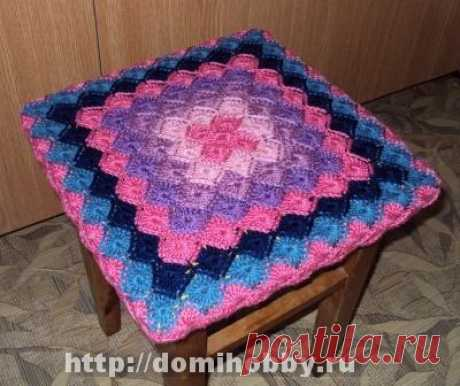 The cover on a stool the Bright cover on a stool is connected by a popular pattern for a plaid. The pattern matches a hook from the center in the form of a square, color of threads changes each two rows thanks to what mosaic drawing from a small square turns out …