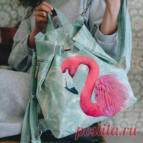 Рюкзак-сумка трансформер с розовым фламинго Рюкзачок из льна в приятных цветах с шикарной птицей фламинго вы можете приобрести в нашем магазине. Каждое изделие мастеров является уникальным, потому что повторить точь в точь ручную работу попросту не возможно. На нашем сайте вы найдете множество интересных вариантов сумок и рюкзаков. А если вдруг у вас появится новая идея росписи для сумки, которой нет ни у кого, то напишите нам и мы воплотим в жизнь для вас любой сюжет.