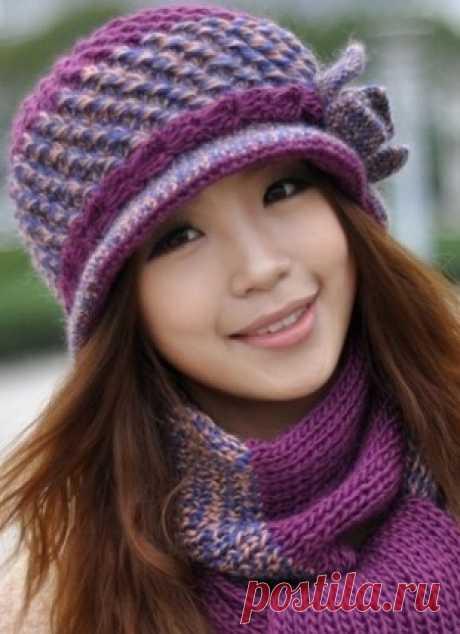 Теплая шляпка - Эфария Очаровательная теплая шляпка, связанная крючком из толстой пряжи. Шляпка дополнена шарфом, связанным из той же пряжи простой лицевой гладью. Шляпа связана из пряжи двух разных цветов: ярко-фиолетовой, фиалковой и сложенной в две нити пряжи васильковой и нежно-абрикосовой. Шляпка имеет маленькие очаровательные поля и украшена сбоку небольшим цветком. Такой фасон шляпы подходит любому типу лица, но