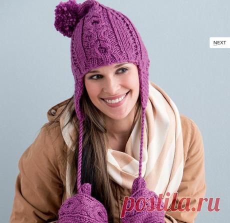 Розовая шапка ушанка спицами с помпонами.