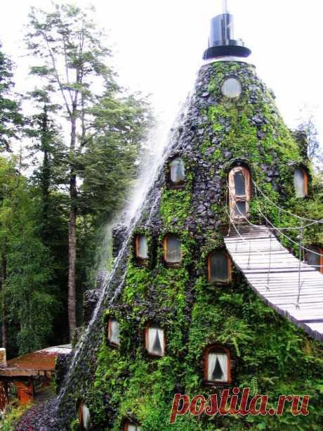 Настоящая экзотика! Похожий на вулкан домик вместо лавы извергает освежающий водопад. Так выглядит отель в Чили. Попасть в отель можно только по подвесному мосту. А заодно и принять душ от брызг воды.;)