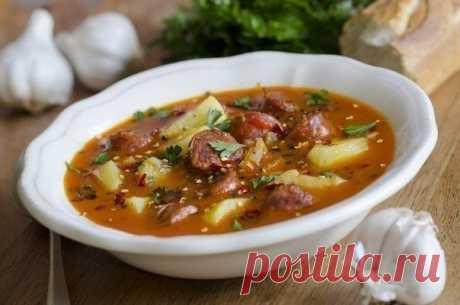 Острый испанский суп с колбасками  Ингредиенты:  Куриный бульон — 4 л Картофель — 4-5 шт. Помидоры — 1-2 шт. Колбаски охотничьи — 3–4 шт. Чеснок — 1–2 зубчика Свежая зелень — по вкусу Болгарский перец — 1 шт. Лук — 1 шт. Паприка — по вкусу Специи — по вкусу  Приготовление:  1. Нарежьте охотничьи колбаски и обжарьте их в сковороде в оливковом масле. 2. Также в сковороду добавьте нашинкованный чеснок, морковь, острые специи, лук, натрите помидоры, порежьте болгарский перец, ...