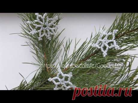 Snowflake from beads on a fir-tree. Weaving by beads for New year. Beadwork.