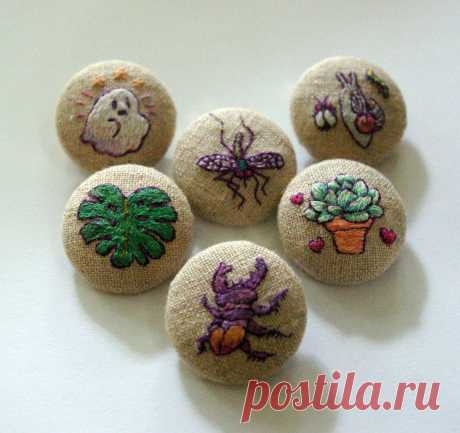 pinback buttons some buttons i recently made, on linen. bashful ghost (just happy to be half-here), mosquito, bug friends (friends all headed towards the same berry probably), split-leaf philodendron (really monstera deliciosa), stag (party) beetle, and a potted succulent!
