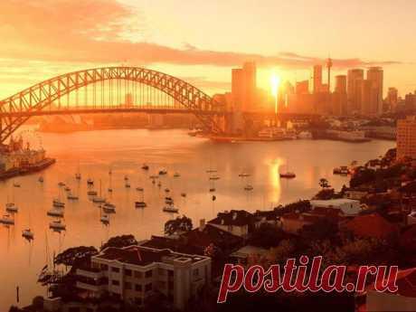 РАССВЕТ НАД ГОРОДОМ. СИДНЕЙ, АВСТРАЛИЯ. Сидней – самый крупный город австралийского континента, основанный в 1788 году английскими колонистами. Первые годы жизни Сиднея прошли в голоде, нищете и беззаконии. Сегодня в Сиднее тепло, весело, беззаботно, спокойно и безопасно. С первого дня в душе человека, попавшего в Сидней, появляется ощущение праздника. Люди здесь живут как бы наоборот: месяц перевернут рогами вверх, север у экватора, юг — у полюса, в августе зима, а в декабре — лето ...