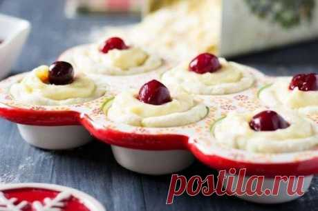 Португальские пирожные  Ингредиенты:  Готовое слоеное тесто — 1 упаковка Яичный желток — 4 шт. Сахарная пудра — 50 г Мука — 40 г Сливки 10-20% — 350 мл  Сахар — 75 г Ванильный экстракт — 1/2 ч. л. Вишня — 24 шт. Миндальные хлопья — по вкусу