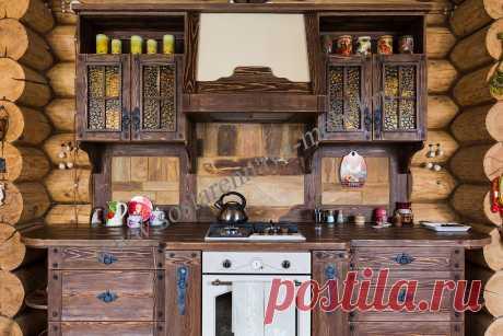Кухня под старину из массива дерева. Коричневый цвет, состаренное дерево, кованая фурнитура. Длина кухни: 2,98 см.  Верхние фасады со стеклом, нижние глухие. Петли и направляющие с доводчиками, внизу выстроенные выдвижные корзины - бутылочницы.  Техника: духовой шкаф, варочная панель, вытяжка.