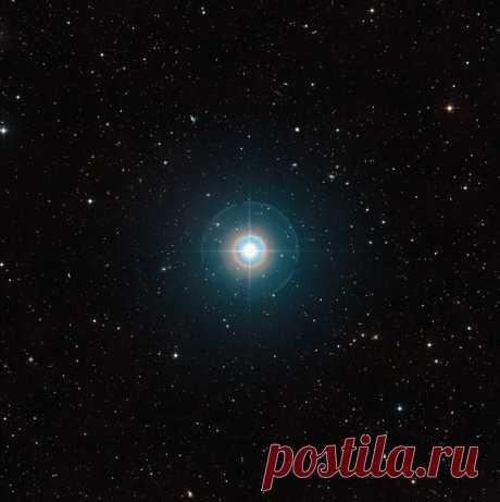 Этот снимок поля вокруг звезды Тау Волопаса взят из обзора Digitized Sky Survey 2. Звезда, которая на небе видна невооруженным глазом находится в центре поля. Лучи и цветные круги вокруг неё искусственные оптические эффекты, связанные с конструкцией телескопа и свойствами фотопластинки. Орбита экзопланеты Тау Волопаса b находится очень близко к звезде и планету на этом снимке заметить невозможно. Её свечение зарегистрировано с помощью телескопа ESO VLT. / Интересный космос