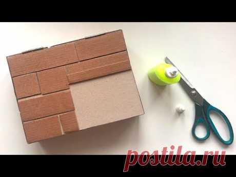 El estuche del cartón por las manos