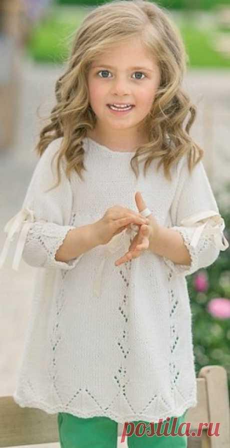 Туника для девочки связана спицами из пряжи белого цвета