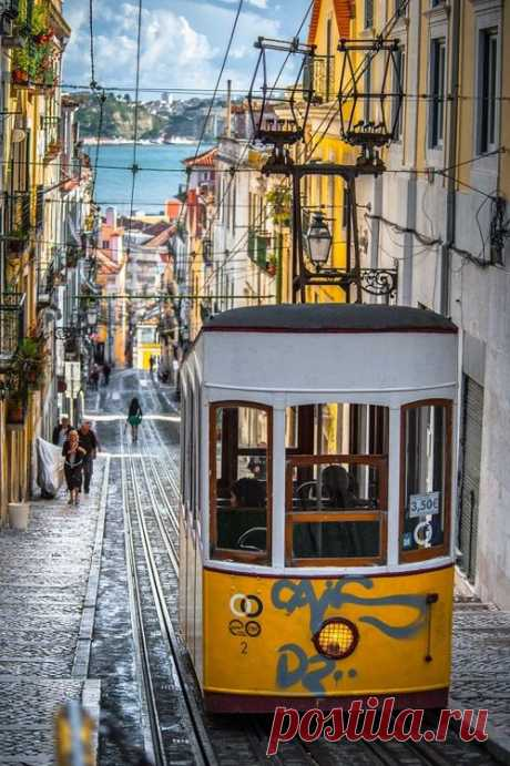La callecita antigua de Lisboa la animadora al océano. Portugal