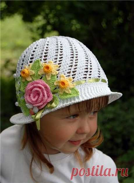 Knitting by a hook. A pretty hat for the girl. Flowers hook