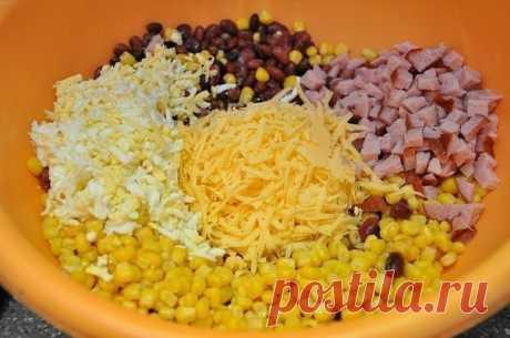 Салат с чесночными сухариками  ИНГРЕДИЕНТЫ:  черствый хлеб для сухариков – 2-3 кусочка, фасоль красная в собственном соку – 1 банка, кукуруза консервированная – 1 банка, сыр твердый – 150 г, корейка копченая – 100 г, яйца вареные – 3 шт., чеснок – 2 дольки, майонез – 200 г, соль и перец – по вкусу  Приготовить сухарики. Для этого хлеб порезать кубиками, обвалять в измельченном чесноке и подсушить на сковороде или в микроволновке.  Яйца натереть, чеснок измельчить, сыр нате...