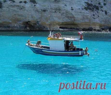 Вода настолько прозрачная, что кажется как будто лодка плывёт по воздуху.  Снимок сделан в ГРЕЦИИ..